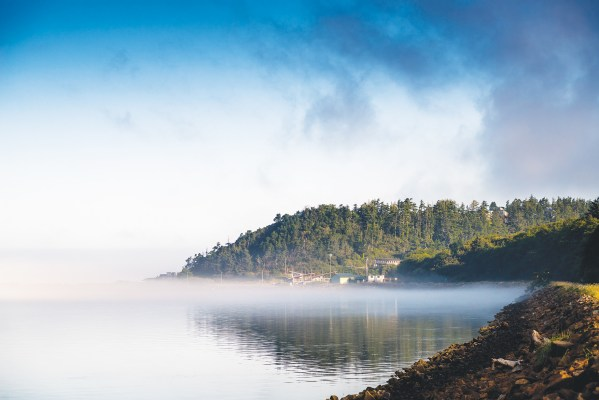 Netarts Bay with low-lying fog, ocean, trees, and a few structures at the water's edge