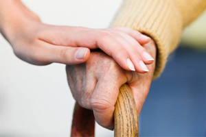 closeup of hand placed upon another hand which is holding a walking cane