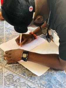 Comrade Efemena Umukoro signs the condolence register.