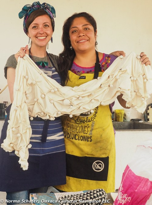 Rhiannon and Elsa hold finished shibori -- to be dyed with indigo