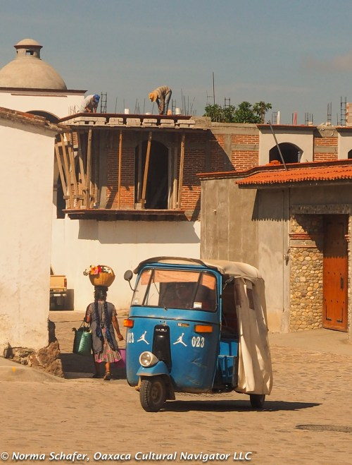 Village tuk-tuk carries shoppers who don't carry baskets on their heads.