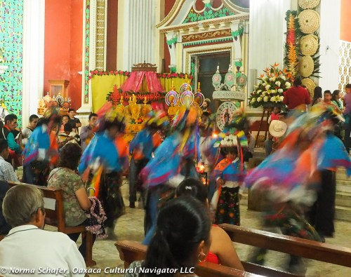 Inside the church, at the altar, a frenzy of dance movement, drum beating