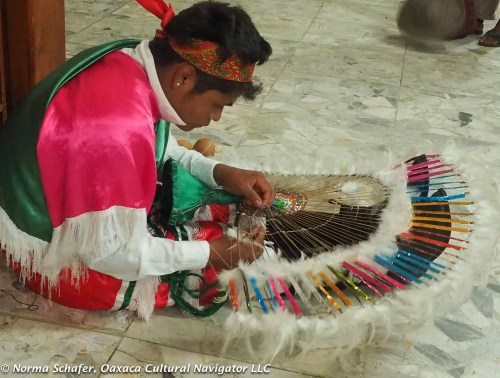 Repairing the feather headdress before joining into the next blessing dance