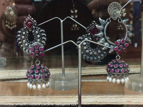 Example of ornate silver earrings inlaid with garnets and embellished with pearls.