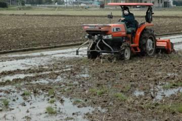 前で肥料を振って後ろでかき混ぜる。