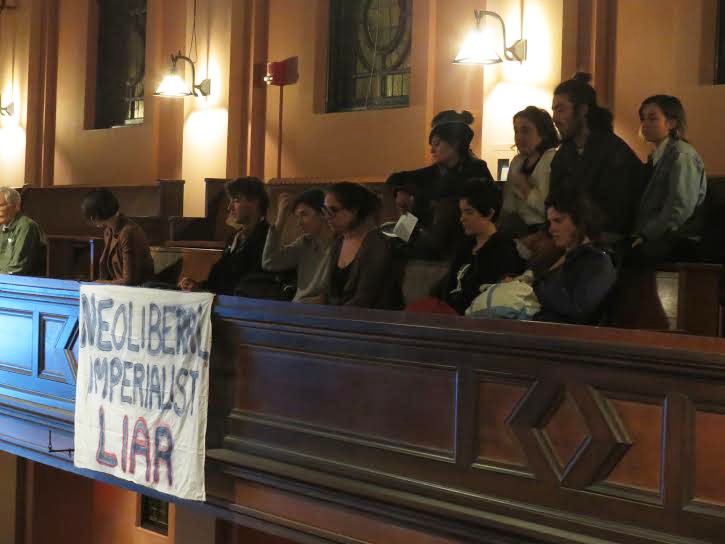 "Students protest Jeffrey Sachs at Wednesday's convocation. Protesters entered Finney Chapel during Sachs's talk to speak out against his actions and the College's decision to fund a speaker the protesters called a ""neoliberalist capitalist."""