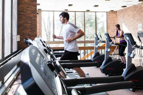 College senior Evan Lowry and Conservatory senior Jackie Meger exercise in Philips gym. The gym recently cancelled its women, trans and non-binary hour.