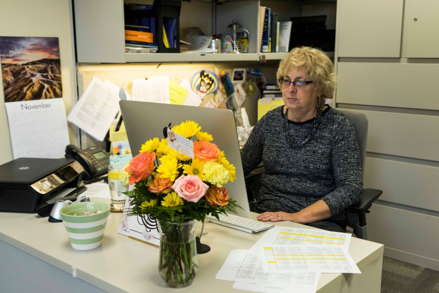 History+department+administrative+assistant+Kathy+King+works+behind+a+bouquet+of+flowers+bought+by+faculty+to+show+support+for+her+and+Religion+department+administrative+assistant+Brenda+Hall.+Administrative+assistants+have+recently+had+to++ll+out+questionnaires+on+the+work+that+they+do+since+the%0ACollege+plans+to+restructure+positions.