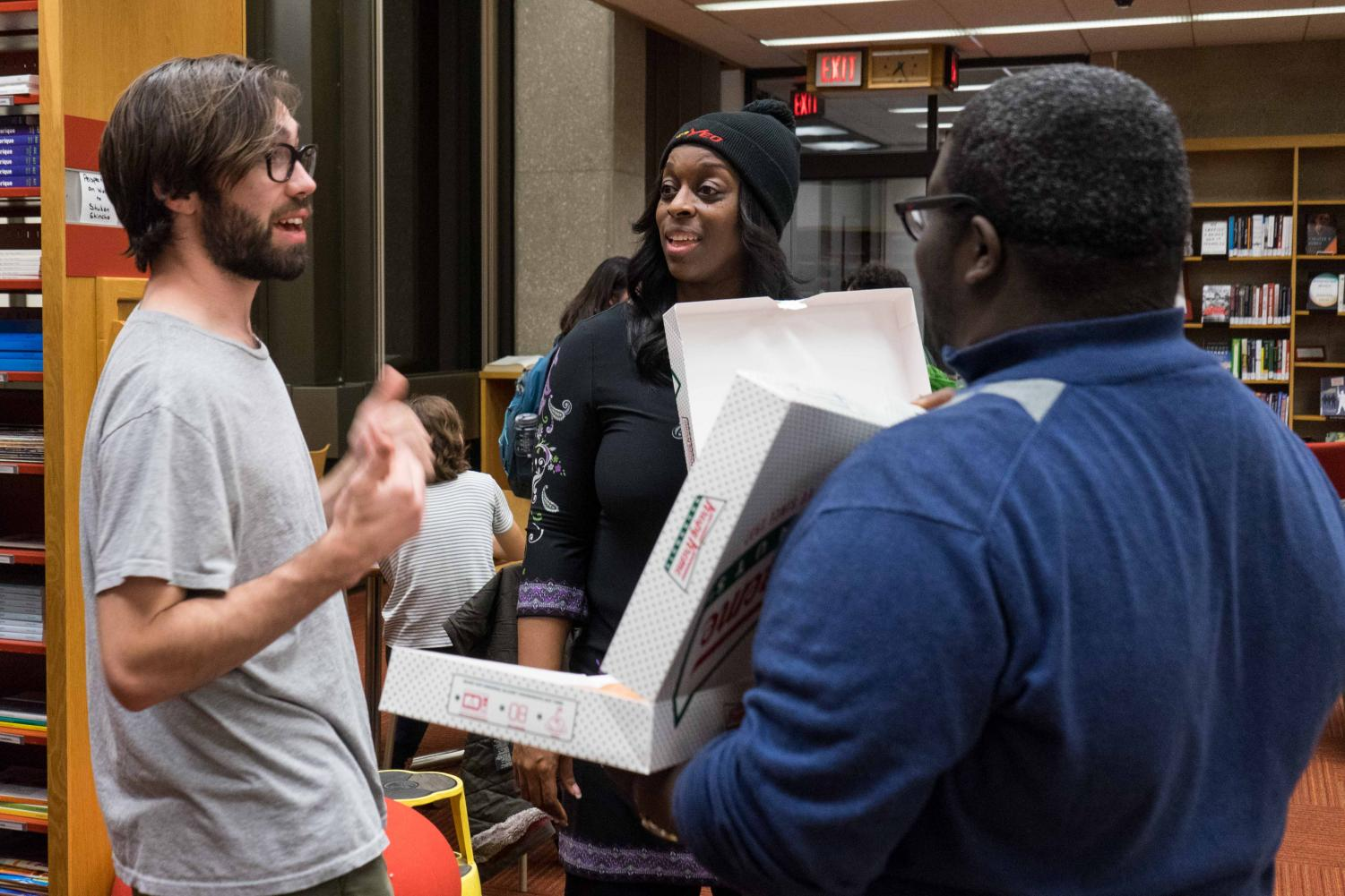 College senior Paddy McCabe discusses a survey he took on his desired campus improvements with Student Senate Vice Chair Kameron Dunbar and President Carmen Ambar. Students who participated received a free Krispy Kreme donut.