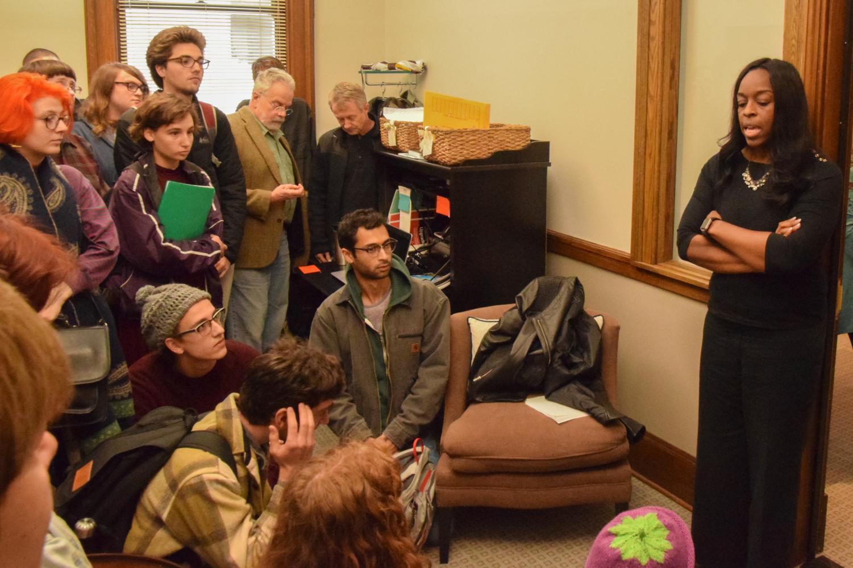 Demonstrators requesting Tom Reid's reinstatement confront President Ambar in her office.