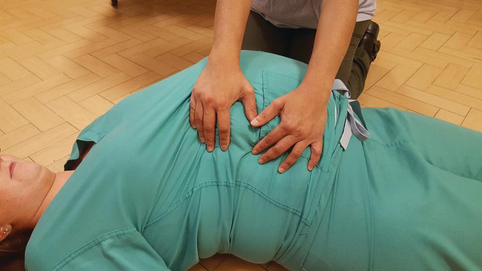 Photo demonstrating manual uterine displacement, wherein the practitioner's hands are cupping and lifting the uterus upwards and to the left off the maternal vessels of a patient lying on the floor.