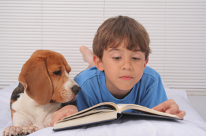 Kid with his dog reading a book in bed
