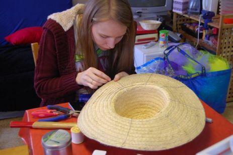 Pour commencer, Caroline renforce en cousant du fil de fer la partie large du chapeau