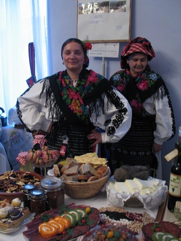 Suzana Mikanović prestavlja se u svečanoj nošnji svoga sela i s punim stolom proizvoda sa svoje okućnice (Snimila Božica Brkan / Acumen)