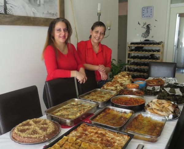 Mirela i Ines s punim stolom jela za predstavljanje Naše male romske kuharice (Fotografija Božica Brkan / Oblizeki)