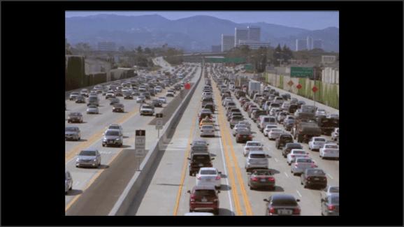 Captura de un vídeo. Tráfco muy denso en una autopista de cinco carriles por sentido