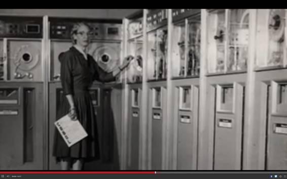 Grace Hopper ante unas cuantas unidades de almacenamiento de la época con un libro sobre COBOL en las manos