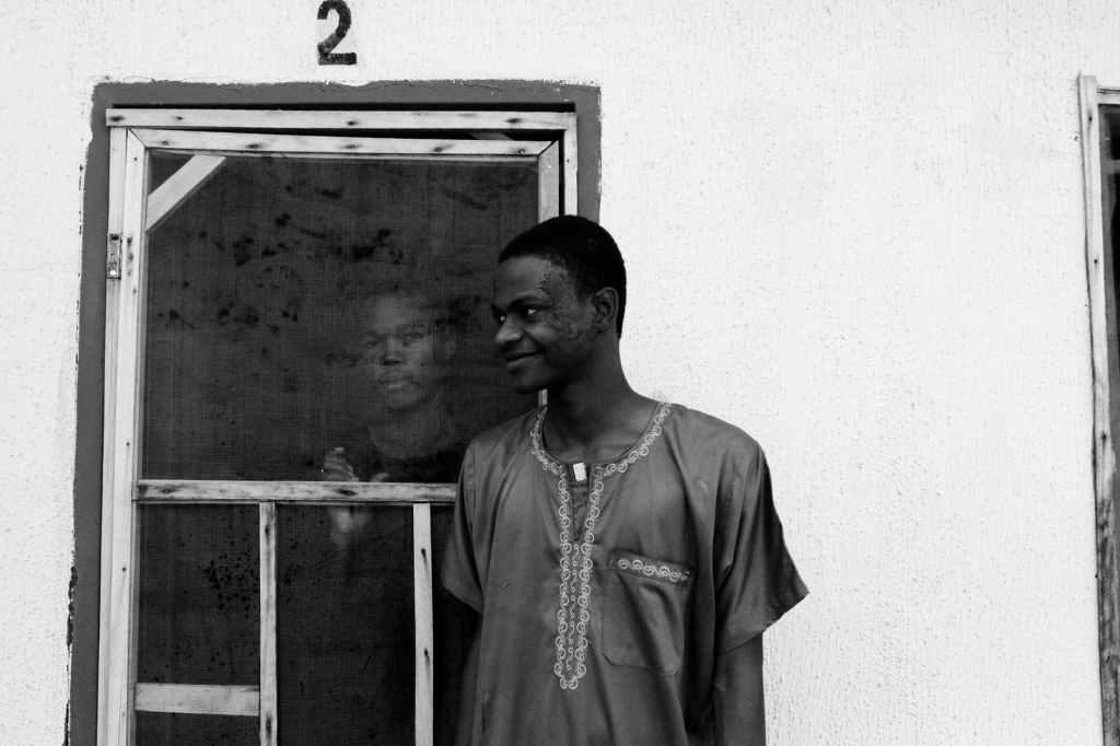 cheerful ethnic man standing near friend looking through window
