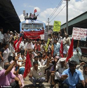 Activists of India stop a train at Guwahati Railway Station during a protest against the hike in fuel prices