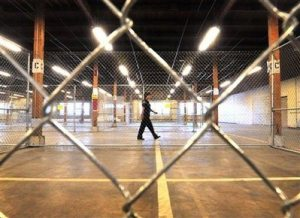 A member of the Denver County Sheriff Dept. walks through the Arrest Processing Site in Denver, Wednesday, Aug. 20, 2008. The 18-cell facility can hold up to 400 people and will be used as a temporary jail during next week's Democratic National Convention.