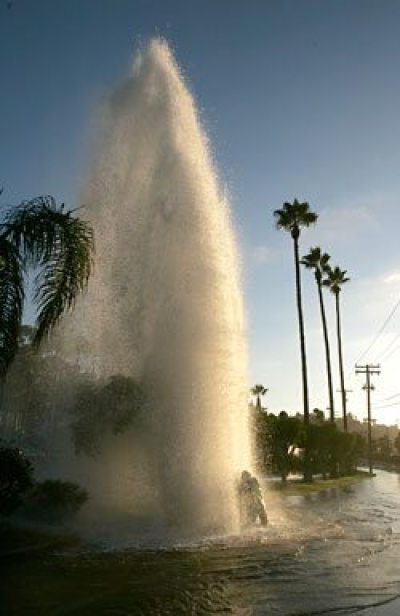 A city water department worker tries to shut off a geyser of water from a broken fire hydrant along Hotel Circle South Wednesday afternoon - EARNIE GRAFTON / Union-Tribune