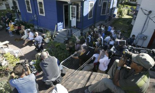 By David Joles, Star Tribune  A throng of media members and interested observers crowd together in a yard next to a house on Iglehart Ave. that was raided by police Saturday afternoon.