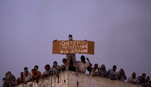 "Holding up a sign that reads, in Spanish, ""We want better treatment by the authorities,"" inmates gather on the roof of a building during the first of two recent riots at La Mesa State Penitentiary in Tijuana. (Guillermo Arias / Associated Press)"