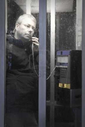11677317-hombre-serio-en-la-cabina-de-telefono-publico-en-la-noche