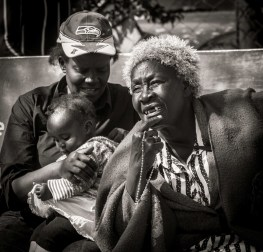 Two Kenyan ladies on a bench with baby, watching the passers-by III
