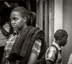 Photograph of young woman and man in the background facing opposite directions - Nairobi