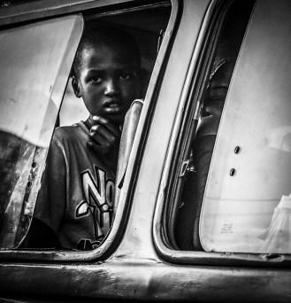 Monochrome photograph of little boy in minibus, departing