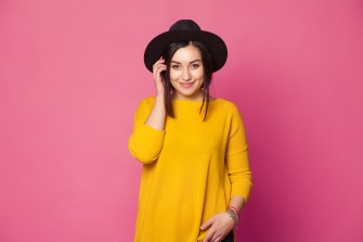 Young healthy woman in a big hat and sweater smiling