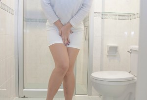 woman holding her crotch and standing in front of the toilet bowl.