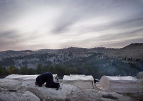 12/01/2013.- A Palestinian man bows in evening prayers in the new 'outpost' called Bab al-Shams (Gate of the Sun), 12 January 2013, erected outside the Palestinian village of Ez Za'im in the contentious E1 area east of Jerusalem (seen on the horizon), in the West Bank known. The Palestinians, joined by some foreign activists are doing this action, they say, as a means of non-violent, peaceful resistance to Israeli expansions of settlements on Palestinians' lands. EFE/EPA/JIM HOLLANDER