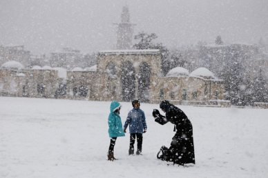 Palestinians stand on the compound known to Muslims as al-Haram al-Sharif and to Jews as Temple Mount in Jerusalem's Old City during a snowstorm January 10, 2013. The worst snowstorm in 20 years shut government offices, public transport and schools in Jerusalem and along the northern Israeli region bordering on Lebanon on Thursday. REUTERS/Ammar Awad