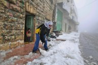 A Palestinian man uses a shovel to clear snow at the entrance of his house in the West Bank city of Hebron, Saturday, Feb. 18, 2012. (AP Photo/Nasser Shiyoukhi)