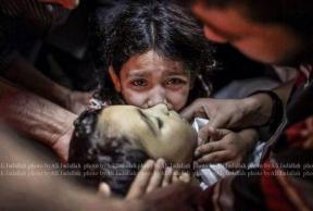 child kisses little baby in Gaza july 2014