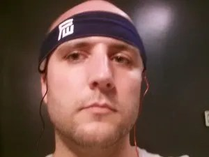 A photo of me wearing the CES device. Essentially just a headband which holds the sponges against one's temples.