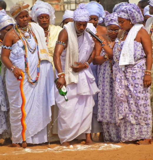 Priest giving libation to gods at Ouidah Festival [Stujarvis.com]