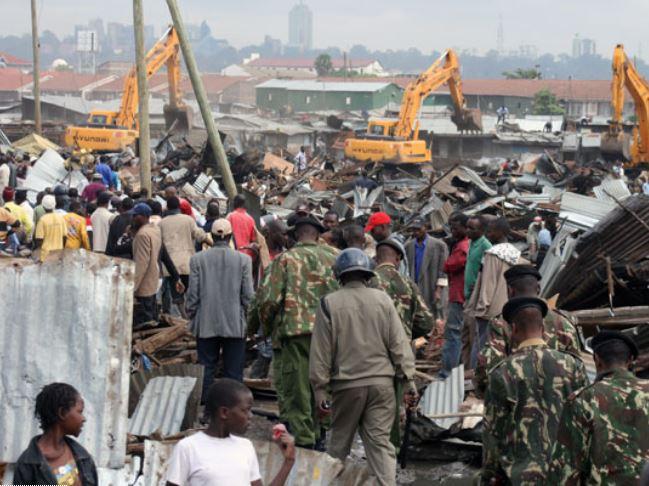Members of the public watch as bulldozers demolish buildings in Nairobi