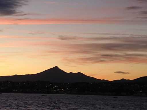Meer, ein Berg und dahinter der Sonnenaufgang