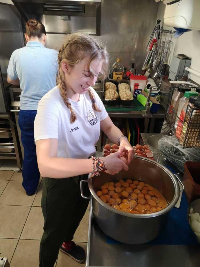 Joana schlägt Eier in einen Topf