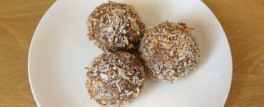 Three round protein balls on a white plate.