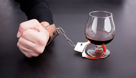 Hand locked to glass of alcohol by handcuffs