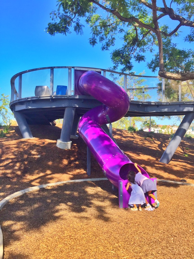 Kids climbing up the tube slide at tree house park in Irvine