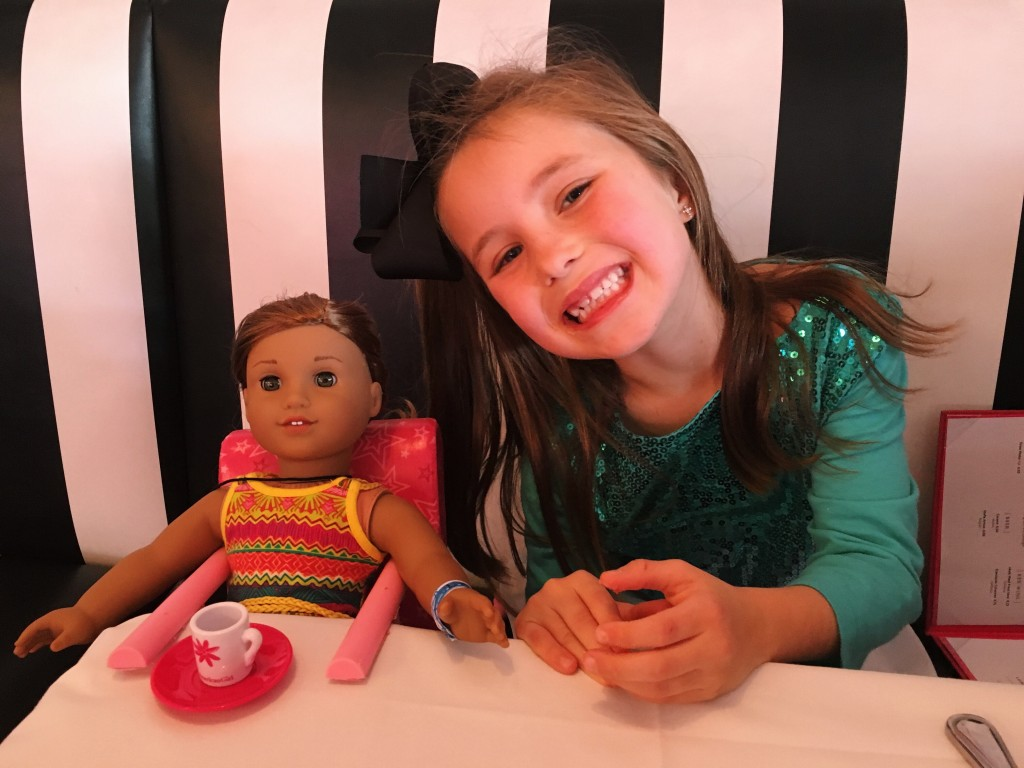 Cute kid with her American Girl Doll