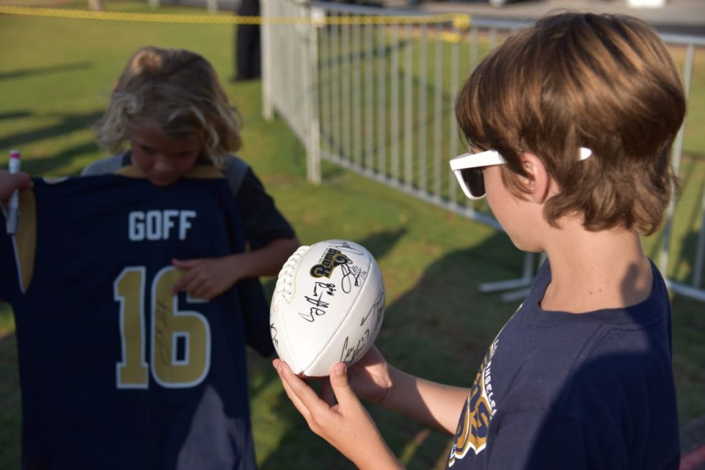 Kids showing their Rams autographs