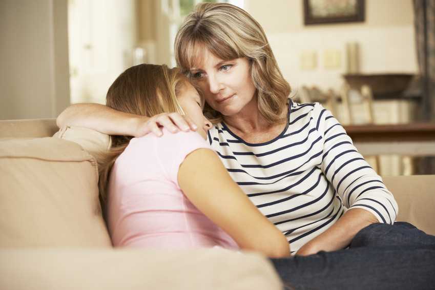 Mother Comforting Teenage Daughter Sitting On Sofa At Home
