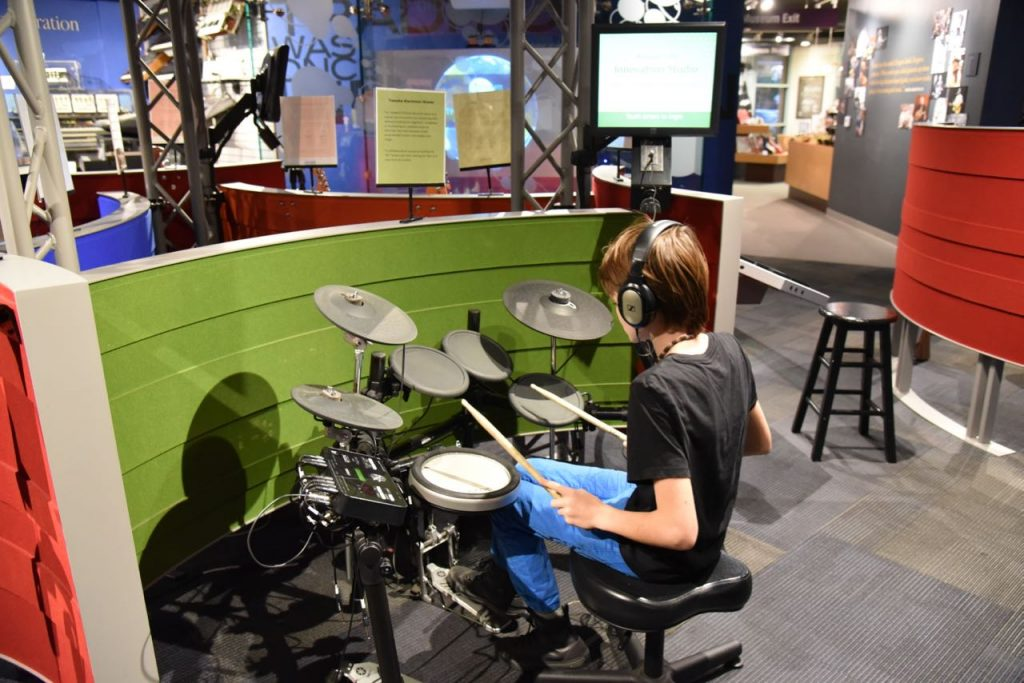 Kid playing the drums at the Museum of Making Music