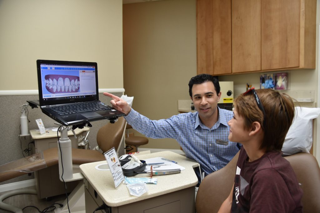 Teenager talking with his Orthodontist about Invisalign Hygiene